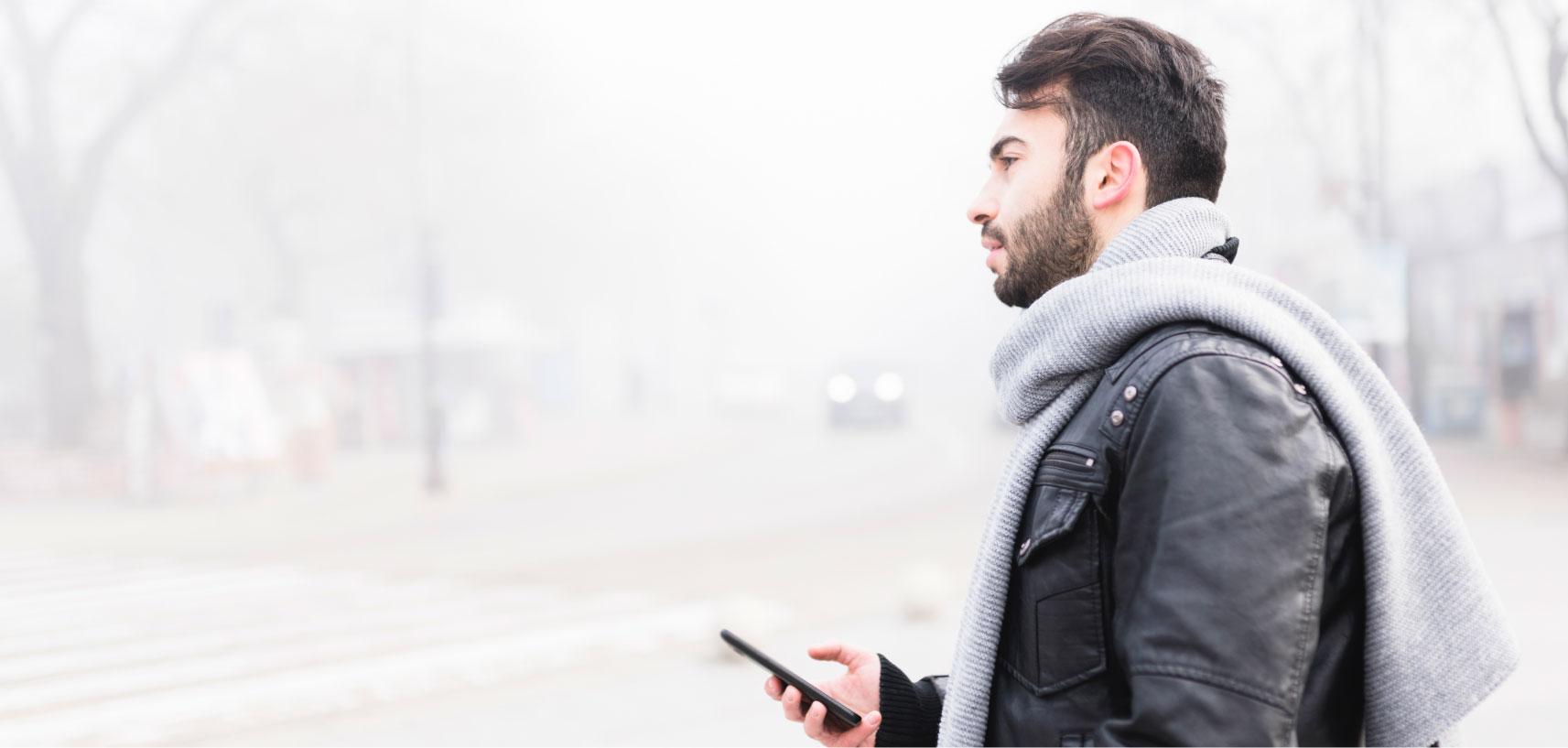 Mann mit Schal benutzt Handy